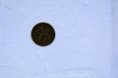 small Russian coin imprinted into the solid ice