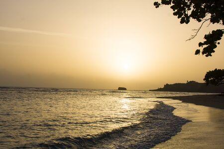 vagues sur le rivage au lever du soleil, avec des collines et des arbres au loin Banque d'images
