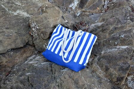 blue and white stripy sand bag on the rocks, with ropes as handles Banque d'images