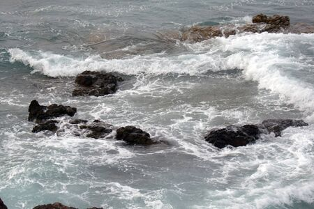 small waves at the stones, crashing with foam against the shore