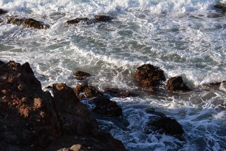 small waves and foam on the brown rocks, by the shore