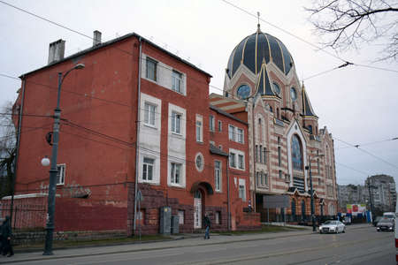 KALININGRAD, RUSSIA - 22.03.2021 building of the synagogue in the city center, with a nearby house and cars in the street