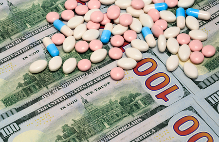 paid medicine: White, blue and pink macro pills and tablets on one hundred dollars banknotes as a background. Money and healthcare still life concept.