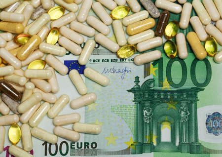 one hundred euro banknote: White and yellow macro pills and tablets on one hundred euro banknote as a background. Money and medicine closeup still life concept.