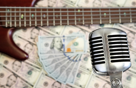 retro microphone: Bass guitar and retro microphone with dollars on money background. Money and music still life concept. Stock Photo