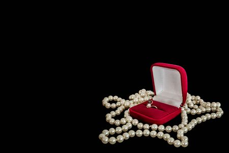 donative: Ring in the red box and a pearl necklace on a black background. Left blank background for text. Stock Photo