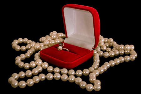 donative: Ring in a box. Ring in the red box and a pearl necklace on a black background.