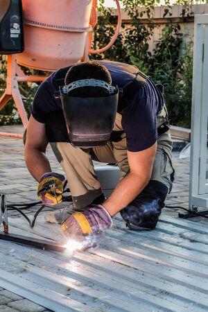soldadura: Soldador suelda marco de perfil de acero para la fabricaci�n de stand generador el�ctrico. Montaje de soldadura por arco al aire libre.