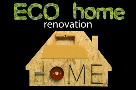 gable home renovation: Eco renovation home. Fixing materials and tools on a sheet of OSB in the form of home. Isolated objects on a black background. Stock Photo
