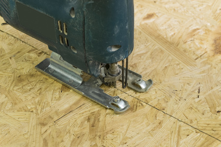 Electricsaw cutting a sheet of OSB