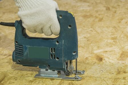 electric material: Cutting sheet OSB electric jigsaw. Man directs the hand tool.