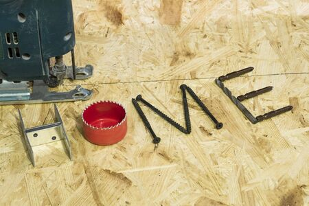 collet: Old electricfretsaw in working position on the background of OSB. The word house made up of fastening materials