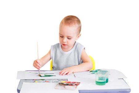 rapturous: Little boy makes his first drawings in watercolor. Isolated on a white background. Stock Photo