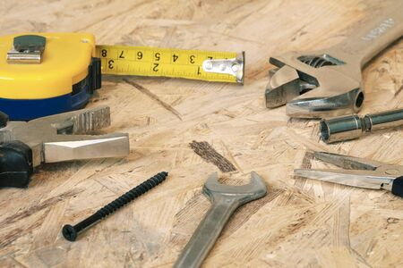 yardstick: The working tools for construction and repair of house: tape measure (yardstick), wrench, screwdriver, pliers, spanner, screw. Photos with limited depth of field.