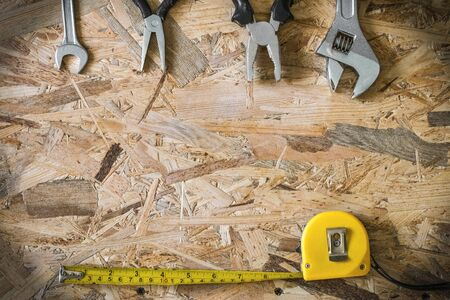 yardstick: The working tools for construction and repair of house: tape measure (yardstick), wrench, pliers, spanner. Photo with copy space and vignetting effect. Stock Photo