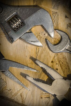 close fitting: The working tools for construction and repair of house: monkey wrench (screw wrench), pliers, spanner. Photo with vignetting effect. Vertical orientation. Close-up.