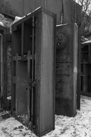 cold war: Nuclear bunker. Nuclear bomb shelter. Old abandoned Soviet Cold War bunker in forest. Upcoming reinforced steel hopper gates. Black and white photo.