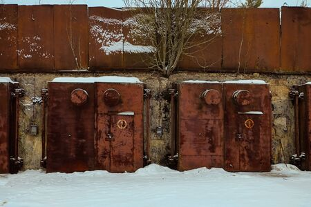 cold war: Nuclear bunker. Nuclear bomb shelter. Old abandoned Soviet Cold War bunker in forest. Locked steel gate with ventilation vents.