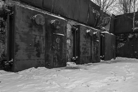 nuclear bomb: Nuclear bunker. Nuclear bomb shelter. Old abandoned Soviet Cold War bunker in forest. Locked steel gate with ventilation vents. Black and white photo.