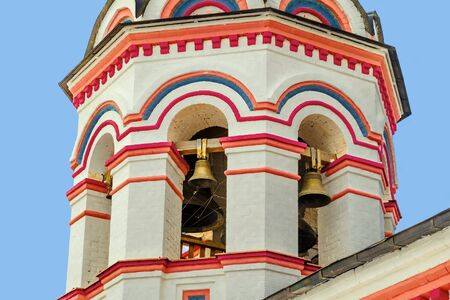 Architecture and exterior bell tower of old orthodox church. Belfry and tier ringing. Masonry temple bell tower.