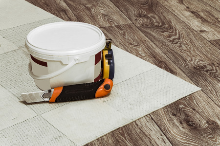 Tool and a container of glue for laying linoleum flooring. Stock Photo
