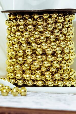 aureate: Golden (aureate) balls. Christmas decoration. Chain golden ornamental beads on a reel. Stock Photo