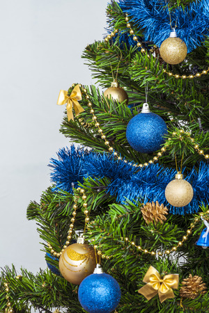 odd jobs: Christmas decorations on a green artificial fir. Golden and bright blue on a green background. Fragment. Photo with limited depth of field.