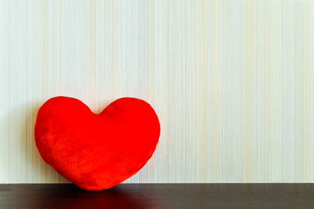wenge: Red fabric heart on a wooden surface wenge color on the background wall with texture in a vertical strip. Love concept. Background with copy space. Stock Photo