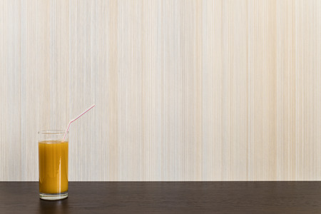 wenge: Glass of juice with straw on a wooden surface wenge color on the background wall with texture in a vertical strip. Minimalism. Background with copy space.