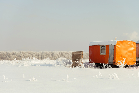 Construction trailer left in the snow. Caravan in winter field. Site container. Stock Photo