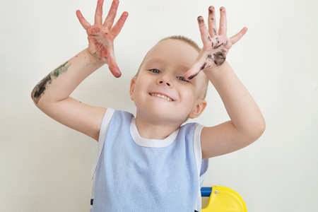 Little boy covered in paint naughty and waving hands. Mischievous child. Stock fotó - 65243348