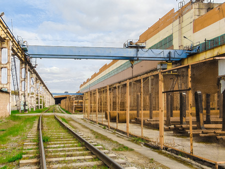 trestle: Industrial area. Outdoor crane trestle. Electric overhead traveling crane above the open warehouse and loading area with the railway.