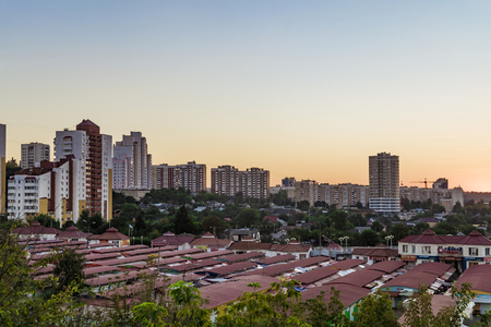 salut: BELGOROD, RUSSIA - SEPTEMBER 10, 2016: Neighborhood of low-rise residential buildings with multi-storey buildings on a slope. Old street market Salut. Evening skyline. Cityscape Belgorod, Russia.
