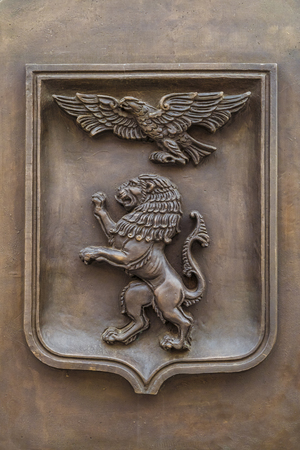 city coat of arms: BELGOROD, RUSSIA - OCTOBER 08, 2016: Cast metal emblem of Belgorod city, Russia. Heraldic shield (coat of arms) with an eagle and a lion.