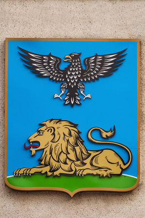 armory: BELGOROD, RUSSIA - OCTOBER 08, 2016: Color coat of arms of the city of Belgorod on a street wall. Heraldic shield with an eagle and a lion.