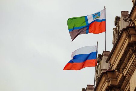 parapet: Flags of the Russian Federation and the Belgorod region waving on the parapet of the administrative building of the Soviet Stalinist architecture