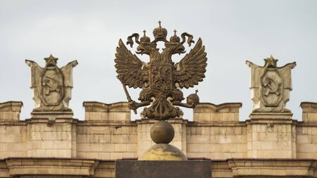 totalitarianism: Coat of arms of the Russian Federation. Coat of arms  on the background of the parapet of the administrative government building with Soviet symbols. Focus on the two-headed eagle.