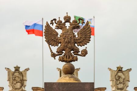 soviet flag: Coat of arms Russian Federation. Coat of arms on background of parapet administrative building government with USSR symbols, flags of Russia and Belgorod region. Focus on the two-headed eagle.