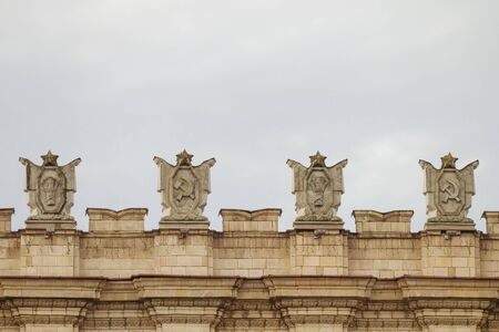 totalitarianism: Fragment of parapet administrative government building with USSR symbols . Posters with the hammer and sickle, a sheaf. Ornament of the Stalinist Empire style of architecture.