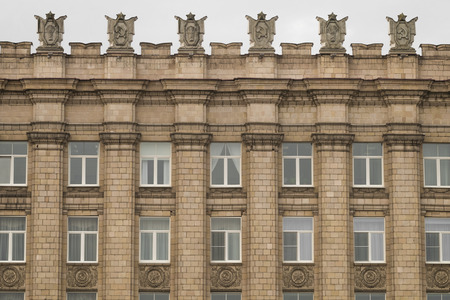 totalitarianism: Fragment of facade building administrative government Belgorod region with USSR symbols . Emblems with the hammer and sickle, a sheaf. Ornament of the Stalinist Empire style of architecture.