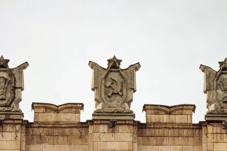 polity: Fragment of parapet administrative government building with USSR symbols. Emblem with the hammer and sickle. Ornament of the Stalinist Empire style of architecture. Stock Photo