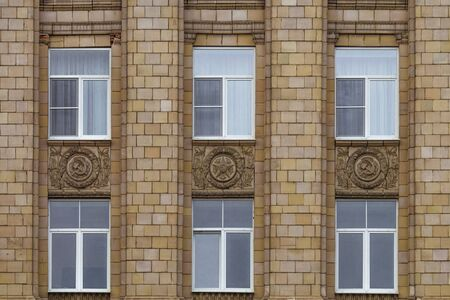 totalitarianism: Fragment of facade building administrative government Belgorod region with USSR symbols. Ornament of the Stalinist Empire style of architecture.