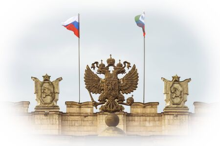 Coat of arms Russian Federation. Coat of arms on background of parapet administrative building government with USSR symbols, flags of Russia and Belgorod region. Focus on the two-headed eagle. Photo with vignetting effect. Editorial