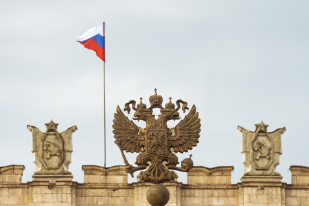 Coat of arms Russian Federation. Coat of arms on background of parapet administrative building government with USSR symbols, flag of Russia. Focus on the two-headed eagle.