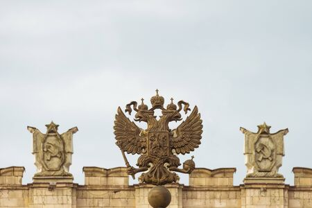 totalitarianism: Coat of arms of the Russian Federation. Coat of arms  on the background of the parapet of the administrative government building with Soviet symbols. Free copy space at the top.