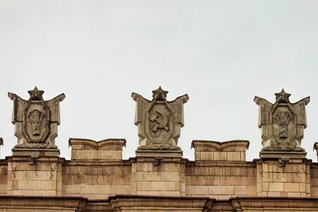 dictatorial: Fragment of parapet administrative government building with USSR symbols . Posters with the hammer and sickle, a sheaf. Ornament of the Stalinist Empire style of architecture.