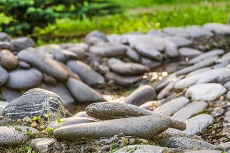 Pebbles at blurred background creek with boulders. Photo with limited depth of field.