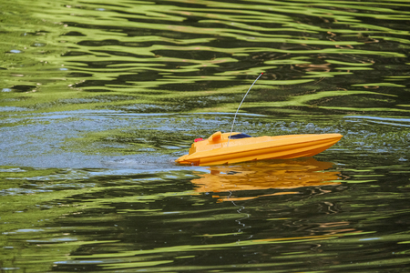 Remote controlled yellow speedboat racing after reversal Stock Photo