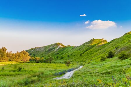 Path at the foot of ridge chalk hills. Green hills under blue sky. The archaeological monument - Krapivinskaya settlement, Belgorod region, Russia. Stock Photo