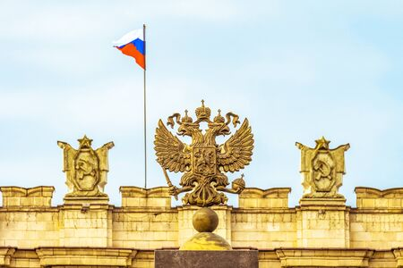 Coat of arms Russian Federation. Coat of arms on background of parapet administrative building government with USSR symbols, Russian flag. Selective focus.